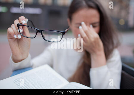 Closeup portrait of attractive female with eyeglasses in hand. Poor young girl has issues with vision. She rubs - Stock Photo