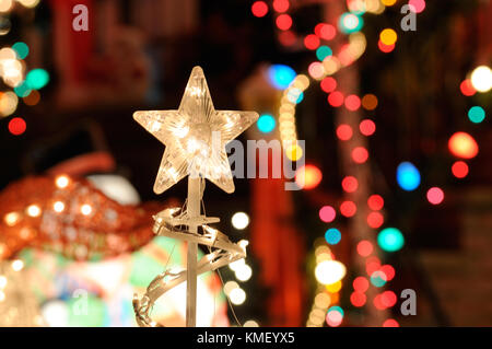Christmas Lights Background. Nativity star, blurred lights and outdoor decorations - Stock Photo