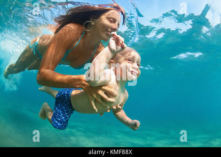 Happy family - mother with baby son dive underwater with fun in sea pool. Healthy lifestyle, active parent, people - Stock Photo