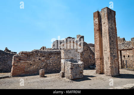 Remains of walls of houses, wells, towers and other ruins in Pompeii, Italy against the blue sky - Stock Photo