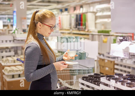 housewife chooses dishes in the store - Stock Photo
