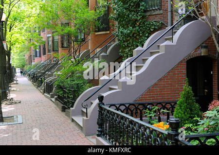 Elegant entry steps of Boston South End row houses. Brick building and sidewalk, iron fences and railings and wavy - Stock Photo