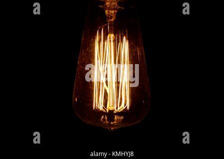 Retro style lightbulb illuminated against a dark background - Stock Photo