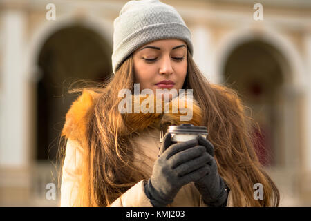 Cheerful cute young woman walking on the street and drinking coffee - Stock Photo