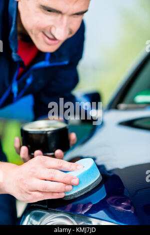 Young man using an absorbent soft towel for drying and polishing the surface of a clean blue car - Stock Photo