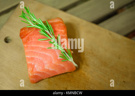 Raw salmon fillet and rosemary on cutting board - Stock Photo