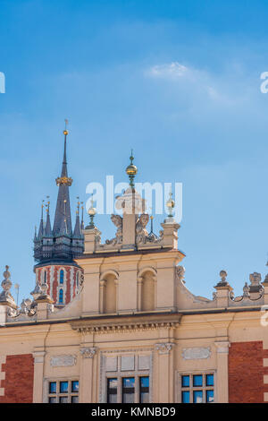 Krakow skyline, view of the gable above the grand portico of 16th Century Cloth Hall with St Mary's Church spire - Stock Photo
