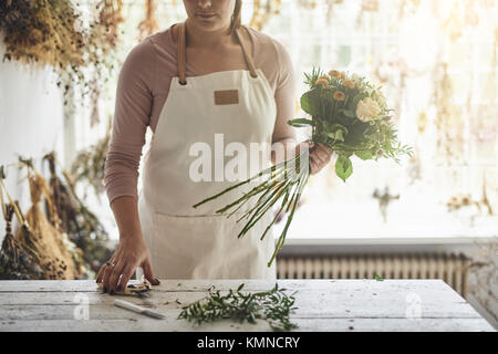 Young woman working at a table in her flower shop trimming the stems of flowers while making a bouquet - Stock Photo