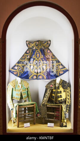 Bullfighter costumes and ´capote´ in Maestranza bullring museum. Seville. Andalusia, Spain - Stock Photo