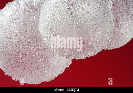 Balls over red background, transparent spheres in white plastic over red background - Stock Photo