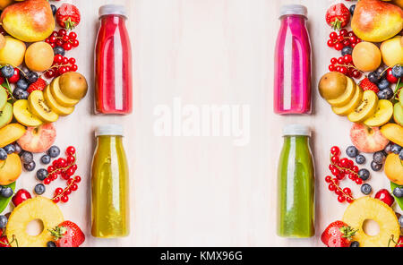 Red,pink,green and yellow smoothies and juices beverages in bottles with various fresh organic fruits and berries - Stock Photo