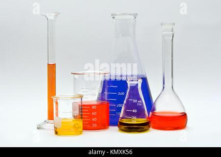Flasks, cylinders and beakers with colorful liquids as pH indicators on a white background - Stock Photo