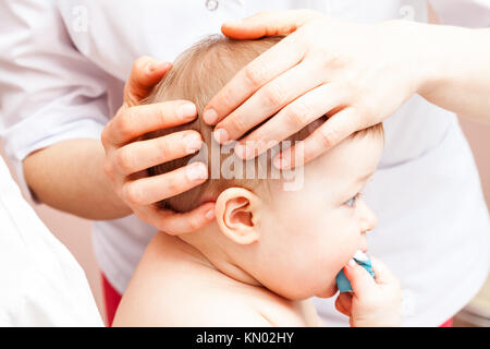 Seven month baby girl's head being manipulated by an osteopath - an alternative medicine treatment - Stock Photo