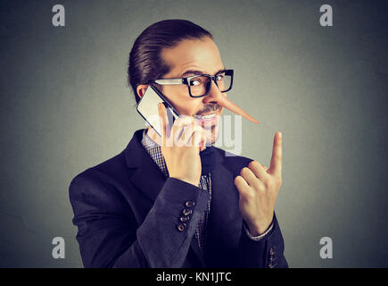 Sly liar business man with long nose talking on mobile phone isolated on gray wall background. - Stock Photo
