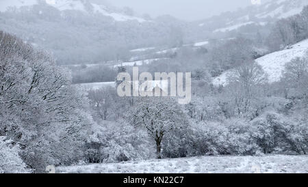 Winter scene with rural country snow landscape in December before Christmas and a cottage nestled in snowy wooded - Stock Photo