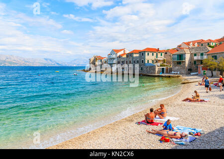 POSTIRA TOWN, BRAC ISLAND - SEP 7, 2017: tourists sunbathing on beach in Postira town with old houses on shore, - Stock Photo