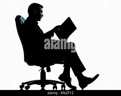 one caucasian business man sitting in armchair reading ancient book silhouette Full length in studio isolated on - Stock Photo