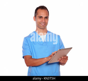 Portrait of a young male in nurse uniform using tablet pc while standing on white background. - Stock Photo