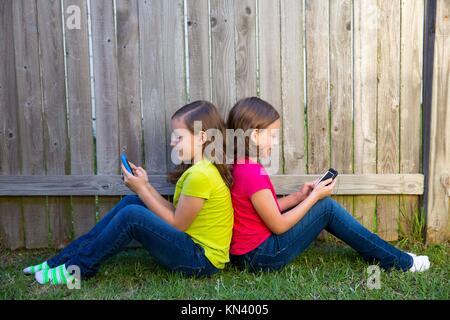 Twin sister girls playing with smartphone sitting on backyard lawn fence leaning on her back. - Stock Photo