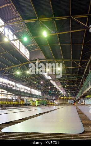 steel plate on conveyor inside of plant. - Stock Photo