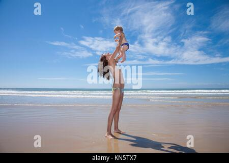 one year baby swimsuit fly in bikini woman mother arms at beach next to Conil Cadiz Spain. - Stock Photo
