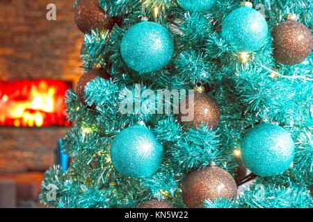 Christmas tree in blue fireplace in background. - Stock Photo
