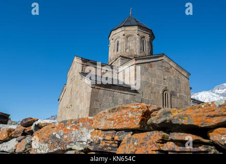 14th century Holy Trinity Church (Tsminda Sameba) near Mount Kazbek in Georgia. - Stock Photo
