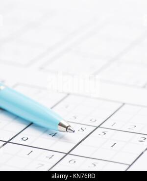 Closeup of sudoku puzzle and pen. Conceptual image of problem solving, finding solutions and intelligence. - Stock Photo