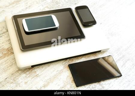 Various smartphones, a Laptop and Tablet Pcs on a wooden Table.. - Stock Photo