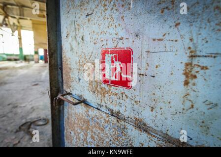 Emergency exit sign in abandoned Jupiter Factory in Pripyat ghost town of Chernobyl Nuclear Power Plant Zone of - Stock Photo