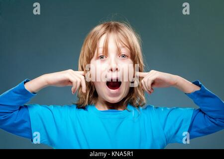 Boy Putting his Index Fingers in his Ears not to Hear. - Stock Photo