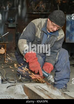 Worker grinds a metal rail for subsequent welding. The photo shows the sparks from the grinding wheel. - Stock Photo