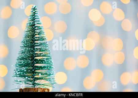 A Christmas tree on the background of a bokeh glowing garland and white boards. Merry Christmas, ideas for postcards - Stock Photo