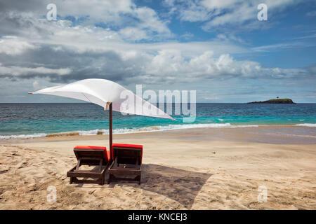 Sun beds and umbrella for rent on White Sand Beach (Pantai Bias Putih). Manggis subdistrict, Karangasem Regency, - Stock Photo