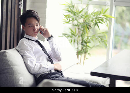 A young Asian businessman is waiting for a partner in a cafe. Bu - Stock Photo