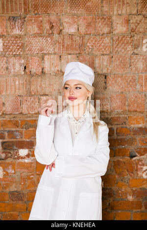 Portrait of a good looking young blond nurse with her arms crossed in a white background - Stock Photo