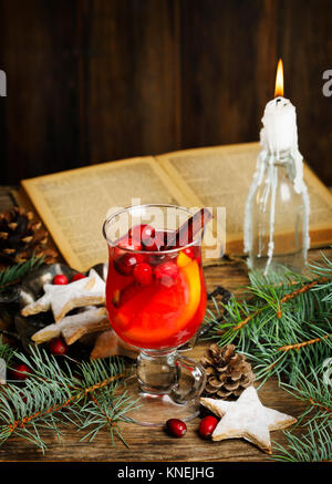 Cranberry and orange tea and star cookies with a candle and book - Stock Photo