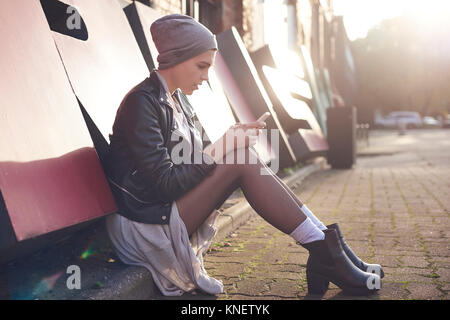Cool young woman sitting on city street looking at smartphone - Stock Photo