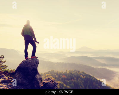 Nature photographer in the action.  Man silhouette above a misty clouds,  morning hilly landscape. - Stock Photo