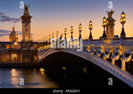 Pont Alexandre III Bridge and illuminated lamp posts at sunset with view of the Invalides. 7th Arrondissement, Paris, - Stock Photo