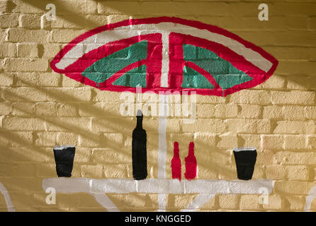 Symbolic art on a exterior public house wall showing the outdoor drinking area in summer - Stock Photo
