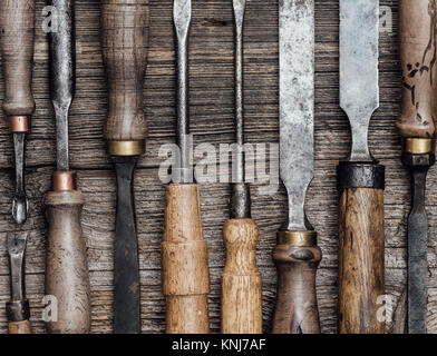 Set of used professional carving and woodworking tools on the workbench close up: carpentry, craftsmanship and handwork - Stock Photo