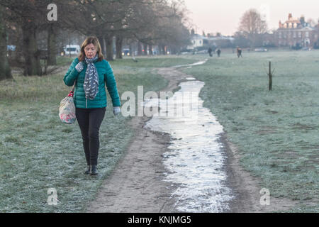 London UK. 12th December 2017.  Morning walkers  on Wimbledon Common covered in large Ice patches as temperatures - Stock Photo