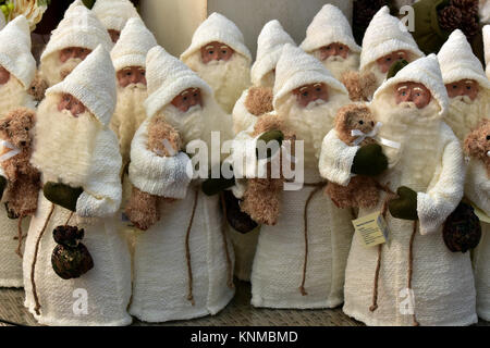 A crowd of Santa Claus or Father Christmas models or toy decorations on a shelf for sale in a christmas store on - Stock Photo