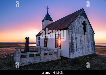 Sun shines through church at sunset in Iceland - Stock Photo