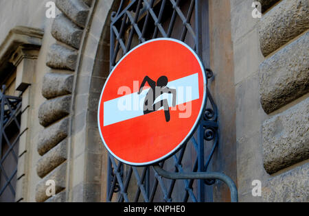 red no entry sign with graphic illustration of man climbing through horizontal white rectangular box - Stock Photo