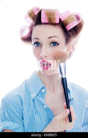 Junge Frau mit Puderpinsel und Lockenwicklern im Haar  - woman with make-up brush and hair roller - Stock Photo