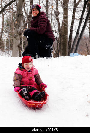 A little girl (3 yr old) sledging in Quebec, while mum looks on - Stock Photo