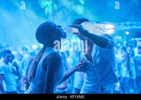 young man giving woman a shot of vodka at music festival Starbeach Dress In White Party in Hersonissos, Crete, Greece, - Stock Photo