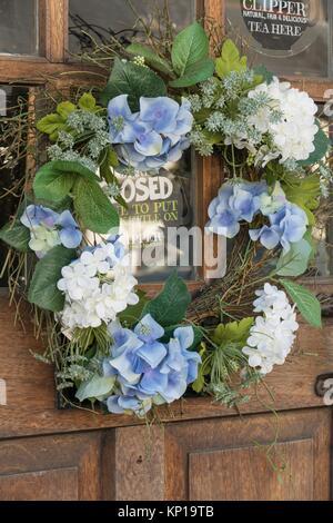 Flower garland on wooden door of English tea shop in Dunster, Uk. - Stock Photo